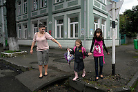 A young woman crosses the street with two children in Batumi...