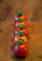 Row of cherry tomatoes on a table.