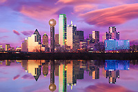 Illuminated by a blend of ambient and artificial light, sunset shimmers off the Dallas skyline as the city is reflected back in the flooded Trinity River. As the sun dips below the horizon, Bank of America Plaza (centered) glows neon green while lights on the iconic Reunion Tower (center left) flash and sparkle, bringing the city to life as the night quickly approaches.