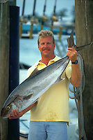 A fisherman smiles proudly as he holds his catch - a large amberjack fish.