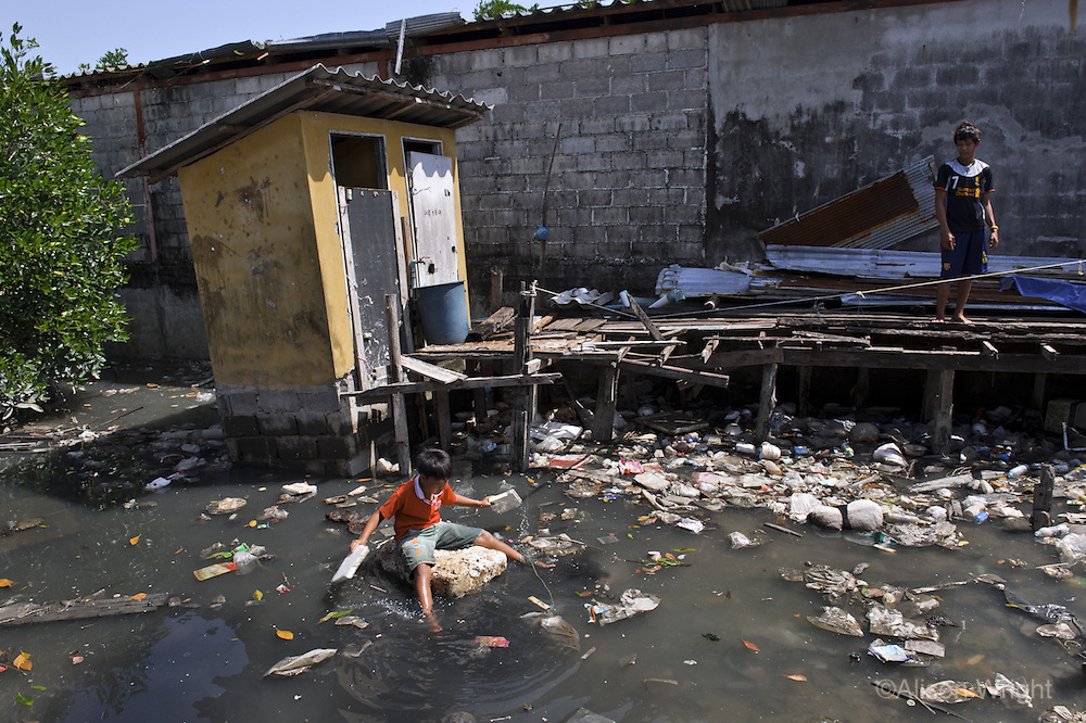 Burmese refugees in Phuket, Thailand. Most of the Burmese in Thailand are not allowed refugee status and live in abysmal conditions at Rashada Pier, leaving the children with limited access to schooling and healthcare. This boy is swimming, as many of the children do, in the filthy stagnant water that surrounds their home. The outhouse that is used as their toilet is in back of him.