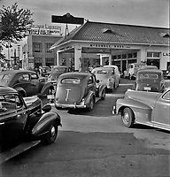 At 7 a.m. on July 21st, the day before stricter gas rationing was enforced, cars were pouring into this gas station on upper Wisconsin Ave. Washington, D.C., 1942.<br /> <br /> Photo by Marjory Collins.