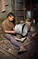 In Casablanca, Morocco, children are employed to make tin pale. Child labor as seen around the world between 1979 and 1980 - Photographer Jean Pierre Laffont, touched by the suffering of child workers, chronicled their plight in 12 countries over the course of one year.  Laffont was awarded The World Press Award and Madeline Ross Award among many others for his work.
