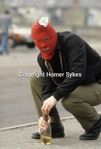 Belfast, Northern Ireland. 1981<br /> A republican youth in distinctive red balaclava with white pom pom makes ready to throw a milk bottle petrol bomb at British Army soldiers during The Troubles.