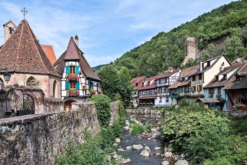 A view down the Weiss River in the Alsatian town of Kaysersberg, showing part of the ancient town wall on the upper right side