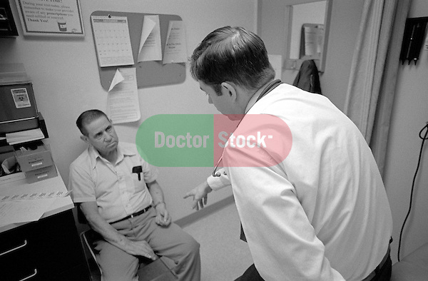 Male doctor pointing to elderly male patient in examination room