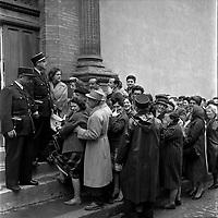 """Affaire de la """"Tournerie des drogueurs""""  JUIN 1961<br /> <br /> Devant le Palais de Justice, rue des Fleurs. 5 juin 1961. Plan moyen de la file d'attente des personnes venues assister au procès (vue de 3/4 face), trois policiers gardent l'entrée du tribunal. Cliché pris dans le cadre de l'affaire de la """"Tournerie des drogueurs"""" dont le procès s'est ouvert à Toulouse le 5 juin 1961. Observation: Affaire de la """"Tournerie des drogueurs"""" : Procès qui s'est ouvert aux assises de Toulouse le 5 juin 1961, sous la présidence de M. Gervais (conseiller doyen). Sur le banc des accusés se trouvent François Lopez, Raoul Berdier, Marie-Thérèse Davergne (Maïté) et d'autres malfaiteurs toulousains (Camille Ajestron, Henri Oustric, Raymond Peralo, Marcel Filiol, Paul Carrère, Charles Davant et François Borja). Outre les accusations pour association de malfaiteurs, ils comparaissent pour l'assassinat de Jean Lannelongue, propriétaire du Cabaret la Tournerie des Drogueurs (rue des Tourneurs) dans la nuit du 3 au 4 janvier 1959, au cours d'une tentative de racket."""