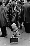 Mother and child St Patricks Day Parade London 1970. The child has taken the mothers handbag that she put on the floor so as too look over the crowd of people more easily.