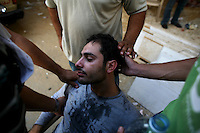 Beirut, Lebanon, Aug 9 2006.Shiyah neighbourhood, Makhbar e Shahideen cemetery,A man collapses during  the funeral of the 39 civilians, many of them women and children, killed on August 7th, when Israeli bombs levelled an appartment building in this non-Hezbollah suburb of Beirut, without any apparent reason.