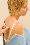 acupuncturist inserts needle in womans back