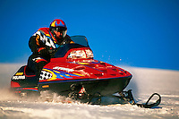 A snowmobile racer drives across the snow with the team logo emlazoned on clothing and machine. competitive sports, snowmobiles, snowmobiling,.