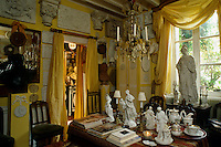 The yellow walls of the drawing room are covered in plaster casts of architectural details and friezes