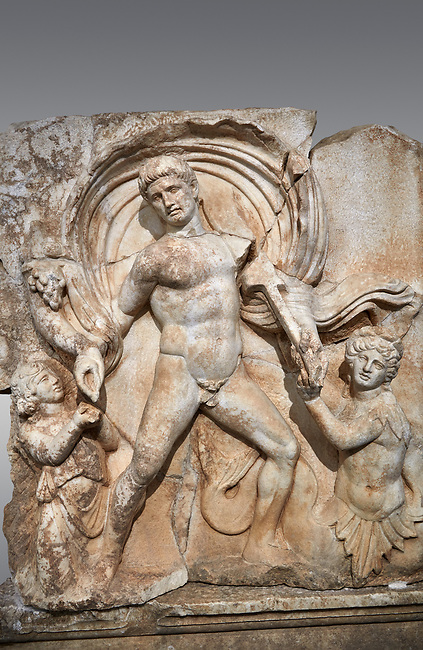 Close up of a Roman Sebasteion relief  sculpture of Emperor Claudius as God of sea and land,  Aphrodisias Museum, Aphrodisias, Turkey. <br /> <br /> The Emperor as god Claudius strides forward in a divine epiphany, drapery billowing around his head. He receives a cornucopia with fruits of the earth from a figure emerging from the ground, anda ship's steering oar from a marine tritoness with fish legs. The idea is clear: the god-emperor guarantees the prosperity of land and sea. The relief is a remarkable local visualisation - elevated and panegyrical - of the emperor's role as a universal saviour and divine protector.