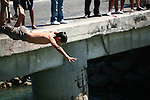 Boy dives off dock into the water below