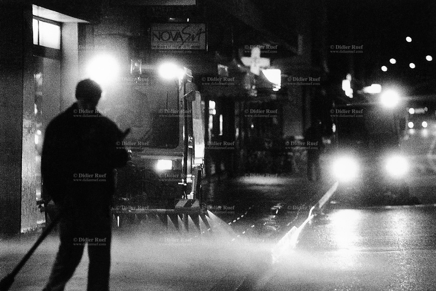 Switzerland. Geneva. Garbage collectors. Streets cleaning.  A street sweeper with his broom, two others workers driving a street brooming machine and a machine washing the road with water, all are cleaning the street in the early morning.  Night time. © 1991 Didier Ruef