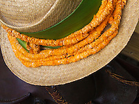 A lei of thousands of tiny orange 'ilima flowers strung together encircles the brim of a woven (lauhala) hat, Hawai'i.