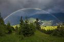 Rainbow over alpine meadows, Nordtirol, Austrian Alps. June.
