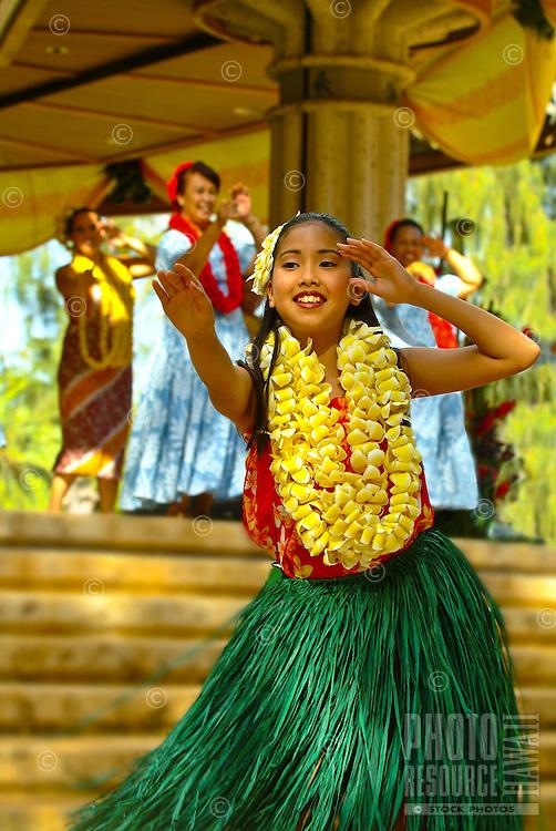 Young hula dancer wearing a grass skirt and plumeria leis at a Lei Day (May 1) auwana (modern or hapa-haole) hula performance at Kapiolani Park, Waikiki Bandstand, Waikiki. Hula is an ancient Hawaiian form of communication.