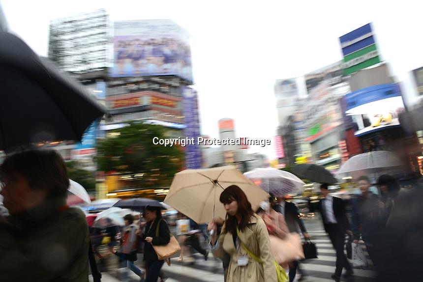 PEOPLE ARE CROSSING WITH UMBRELLA ON SHIBUYA CROSSING NEAR SHIBUYA STATION, TOKYO