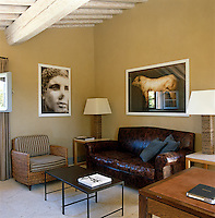 A leather sofa combines with more contemporary furniture in the small study