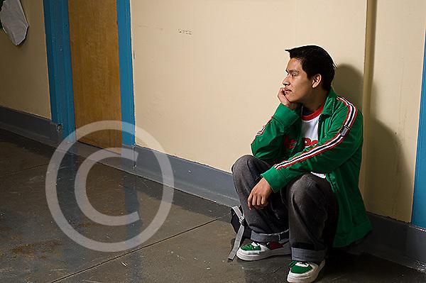 boy sitting alone in high school corridor isolated, alone