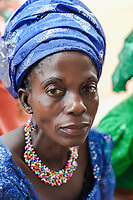 Nigeria. Abakaliki State. Uburu Amach. St. Patrick's Catholic Church. Portrait of a Igbo woman with colorful necklace during the mass celebration for the 25th Priesthood Anniversary of Reverend Father Edward Inyanwachi. The woman wears a head tie which is a women's cloth head scarf. The head tie is used as an ornamental head covering or fashion accessory, or for functionality in different settings. Its use or meaning can vary depending on the country and/or religion of those who wear it. The head tie is called gele in Nigeria. 14.07.19 © 2019 Didier Ruef