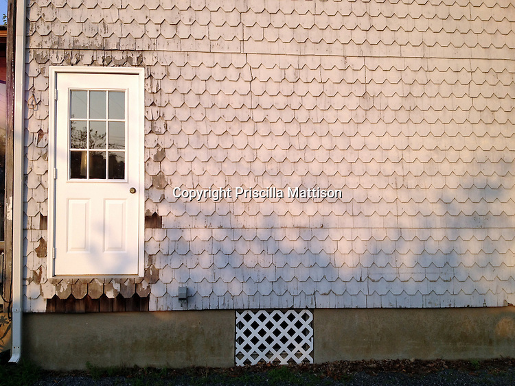Rehoboth Beach, DE - June 20, 2012: Afternoon light falls on the exterior wall of a house with peeling shingles and missing stairs.