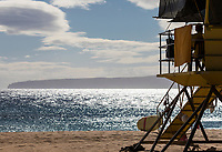 A lifeguard on duty in a lifeguard tower at Makena Beach, Maui, with Kaho'olawe Island in the distance