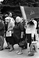 """Russia. Krasnodar Krai Region. Krasnodar. City center. Old people, all communists, stand in from of the town hall. An elderly woman holds in her right hand the State Flag of the Union of Soviet Socialist Republics, and in her left hand a plastic bag with a dog and a beautiful young woman in swimsuit. The State Flag of the Union of Soviet Socialist Republics (commonly known as the Soviet flag), was the official state flag of the Union of Soviet Socialist Republics (USSR) from 1922 to 1991. The flag's design and symbolism are derived from several sources, but emerged during the Russian Revolution. The flag is also an international symbol of the communist movement as a whole. The nicknames for the flag were the Hammer and Sickle and the Red Banner. Another aged woman holds a sign in cyrillic language with the words """" Delegate (legislator or MP) ! Defend the Soviet power """". Krasnodar (also known as Kuban) is the largest city and the administrative centre of Krasnodar Krai in Southern Russia. 30.09.1993 © 1993 Didier Ruef"""