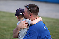 Batavia Muckdogs young fan gets a hug after participating in a wiffle ball home run tournament during the teams pre-season pep rally at Dwyer Stadium on June 15, 2011 in Batavia, New York.  Photo By Mike Janes/Four Seam Images
