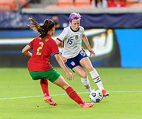 HOUSTON, TX - JUNE 10: Megan Rapinoe #15 of the United States attempts to dribble the around Catarina Amado #2 of Portugal during a game between Portugal and USWNT at BBVA Stadium on June 10, 2021 in Houston, Texas.