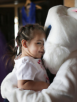 Vera Ennsle, 1, of Rogers hugs the Easter bunny, Saturday, April 3, 2021 at the Oasis of Hope thrift shop Rogers. The Easter Bunny greeted guests for their prom dress and tuxedo sale. Staff gave away free Easter baskets, candy and books. Check out nwaonline.com/210404Daily/ for today's photo gallery. <br /> (NWA Democrat-Gazette/Charlie Kaijo)