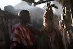 A member of the Masai tribe looks over raw lamb and beef meat hanging in the entrance to a small hut at a market on the outskirts of Arusha, Tanzania on September 24, 2008.  Due to lack of electricity meat is rarely ever refridgerated in Tanzania and East Africa and because of this much of the population lives in close contact with livestock, leaving them suspetible to many health concerns including some neglected tropical diseases such as fascioliasis.