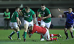 Ireland outside half Steve Crosbie skips through the tackle of Wales prop Nicky Smith..Under 20 Six Nations.Wales v Ireland.Eirias - Colwyn Bay.01.02.13.©Steve Pope