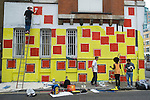 Ben Eine Stencil Street Artist. Creating new work in Middlesex Street London E1 (real name Ben Flynn) Ben at top of ladder, plus his assistant and helpers below.