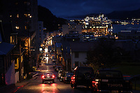 Brake lights of a car on street during a rainy evening in Juneau above the town and the cruise ship.