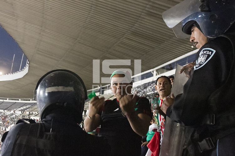Mexican fans heckle USA fans outside the American supporters section protected by Mexican police at Azteca stadium before the USA vs. Mexico World Cup Qualifier in Mexico City, Mexico on March 26, 2013.
