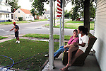 """""""This is the American dream and we are living it,"""" said Marisela Chavez, enjoying a quiet summer evening with Stephanie, 11, one of her three daughters. Chavez came to Beardstown in 1995; she works for the school system's bilingual program and her husband Valentine, left, works at Excel. Like many Mexican families in Beardstown, they purchased a home next to Caucasian neighbors and adopted local customs, such as flying the flag and maintaining their lawn."""