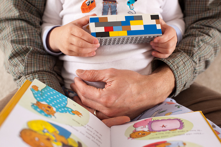 After a Lego-building party, my husband reads to our younger son, age three.