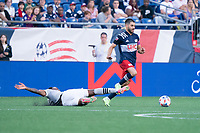 FOXBOROUGH, MA - JULY 25: Mason Toye #13 of CF Montreal slides to tackle Carles Gil #22 of New England Revolution during a game between CF Montreal and New England Revolution at Gillette Stadium on July 25, 2021 in Foxborough, Massachusetts.