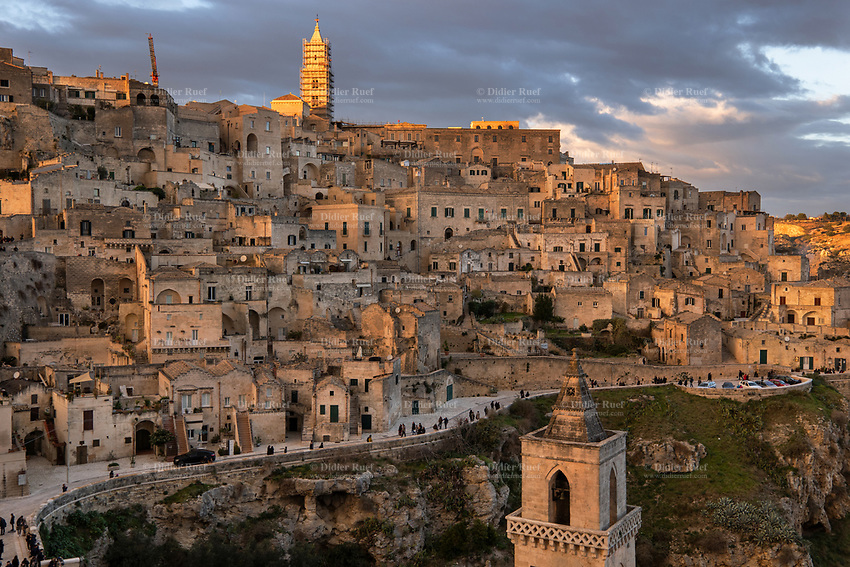 """Italy. Basilicata Region. Sunset on Matera. Known as la Città Sotterranea (""""the Underground City""""), Matera is one of the oldest continuously inhabited cities in the world, having been inhabited since the 10th millennium BC. Its historical centre """"Sassi"""", along with the Park of the Rupestrian Churches, was awarded World Heritage Site status by UNESCO since 1993. The Sassi di Matera are two districts (Sasso Caveoso and Sasso Barisano), well-known for their ancient cave dwellings.The Sassi originate from a prehistoric troglodyte settlement and are suspected to be among the first human settlements in Italy. There is evidence that people were living here as early as the year 7000 BC.The Sassi are houses dug into the calcarenite rock itself, which is characteristic of Basilicata, locally called """"tufo"""" although it is not volcanic tuff or tufa. The streets in some parts of the Sassi often run on top of other houses. The ancient town grew up on one slope of the ravine created by a river that is now a small stream. The ravine is known locally as """"la Gravina"""". In the 1950s, the government of Italy forcefully relocated most of the population of the Sassi to areas of the developing modern city. Until the late 1980s this was considered an area of poverty, since many of these houses were, and in some cases still are, uninhabitable. The current local administration, however, has become more tourism-oriented, and it has promoted the regeneration of the Sassi with the aid of the European Union, the government, UNESCO. Today there are many thriving businesses, pubs, restaurants and hotels. A tour guide or a tourist guide is a person who provides assistance, information on cultural, historical and contemporary heritage to people on organized tours and individual clients at Matera historical sites. On 17th October 2014, Matera was declared Italian host of European Capital of Culture for 2019. Basilicata is a region in Southern Italy. 8.12.18  © 2018 Didier Ruef"""