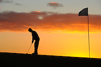 A sillouette of a golfer as he plays at sunset.