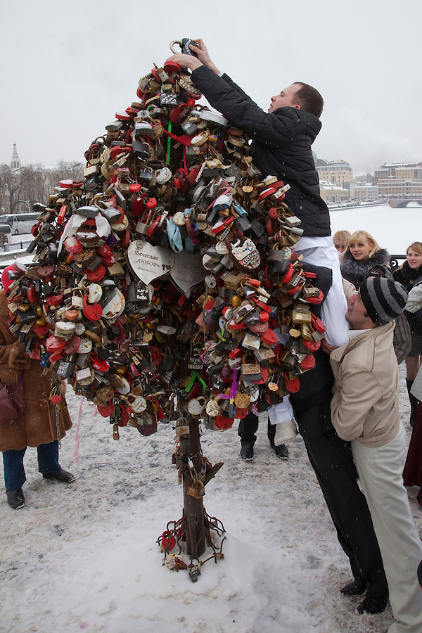 Moscow, Russia, 14/02/2011..Wedding guests hoist a groom hanging a wedding padlock on an artificial tree in temperatures of minus 14C.