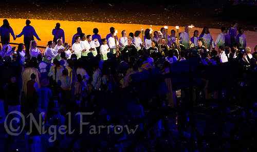 """27 JUL 2012 - LONDON, GBR - Torchbearers (from the left) rower Cameron MacRitchie, athlete Adelle Tracey, sailor Callum Airlie, athlete Desiree Henry, London 2012 Young Ambassador Jordan Duckitt, athlete Katie Kirk (hidden) and athletes Aidan Reynolds jog to the centre of the stadium to light the Olympic Cauldron during the """"There Is a Light That Never Goes Out"""" section of the Opening Ceremony of the London 2012 Olympic Games at the Olympic Stadium in the Olympic Park, Stratford, London, Great Britain .(PHOTO (C) 2012 NIGEL FARROW)"""