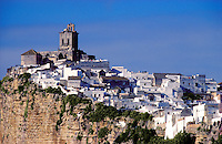 Spain, Andalucia/Andalusia.  The village of Arcos de la Frontera, one of the white towns famed for its remarkable site at the top of a rock face overlooking the River Guadalete, near Cadiz.  The church of San Pedro is a Gothic construction with a Baroque belltower..