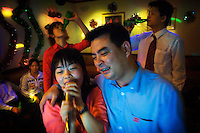 Textile workers and executives from a jeans production factory enjoy beers and karaoke during the Chinese New Year festival.