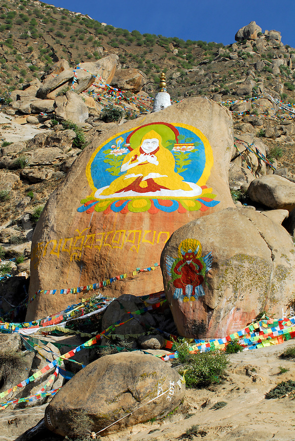 Rock carvings and paintings depict Tsongkhapa, founder of yellow-hat Gelugpa order of Tibetan Buddhists and protector deity Garuda, surrounded by prayer flags on the west side of Drepung Monastery, Lhasa, Tibet, China.