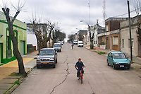 Street scene in the town Progreso, residential area with houses, cars and a moped motor cyclist. Bodega Castillo Viejo Winery, Las Piedras, Canelones, Uruguay, South America