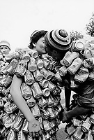 Switzerland. Geneva. A couple kisses during the Lake parade which is a yearly techno event in Geneva. The man and the woman, both are dressed up on their bodies with aluminium cans from soft drinks, such as Coca Cola, Schweppes and Aquarius. Coca-Cola, or Coke is a carbonated soft drink manufactured by The Coca-Cola Company. Originally intended as a patent medicine, it was invented in the late 19th century, whose marketing tactics led Coca-Cola to its dominance of the world soft-drink market throughout the 20th century. The drink's name refers to two of its original ingredients: coca leaves, and kola nuts (a source of caffeine). Aquarius is a mineral sports drink manufactured by The Coca-Cola Company. Schweppes is a Swiss beverage brand that is sold around the world. It includes a variety of lemonade, carbonated waters and ginger ales.© 2005 Didier Ruef