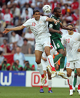 Saudi Arabian defender (6) Omar Al Ghamdi goes up for a header against Tunisian midfielder (10) Kaies Ghodhbane. Saudi Arabia and Tunisia played to a 2-2 tie in their FIFA World Cup Group H match at FIFA World Cup Stadium, Munich, Germany, June 14, 2006.